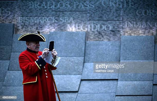 Chelsea pensioner takes a picture on a mobile phone in front of the Australian War Memorial during a dawn remembrance service at the Wellington Arch...