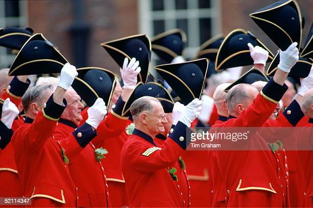 Chelsea Pensioners Dressed In Their Traditional Uniform Of Bright Red Jacket Raising Their Tricorn Hats And Cheering During The Founder's Day Parade...