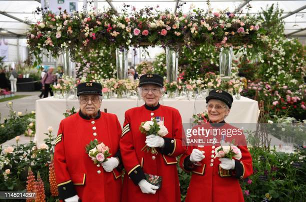 Chelsea Pensioners pose for a photograph with their posies of roses during a visit to the 2019 RHS Chelsea Flower Show in London on May 20, 2019. -...