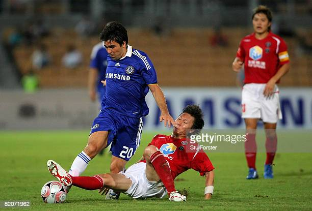Chelsea player Deco is challenged by Blades captain Li Tie during the Macau International Football challenge between Chelsea and Chengdu Blades FC at...