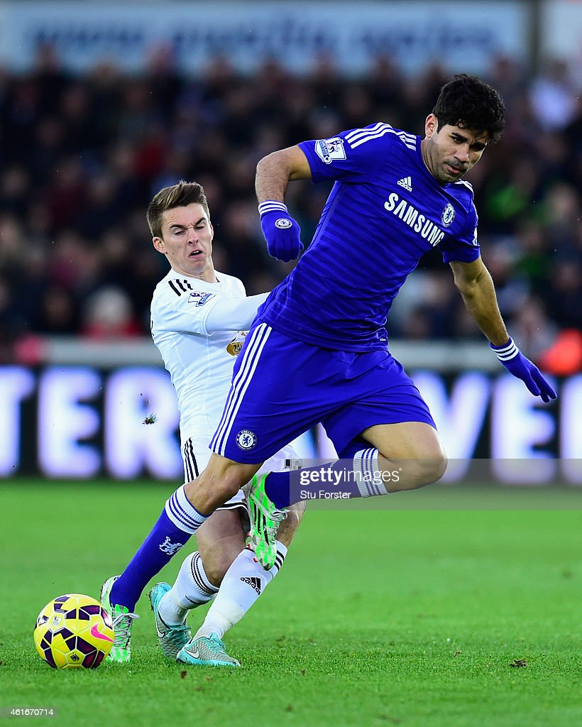 Chelsea player Diego Costa is challenged by Tom Carroll of Swansea during the Barclays Premier League match between Swansea City and Chelsea at Liberty Stadium on January 17, 2015 in Swansea, Wales.