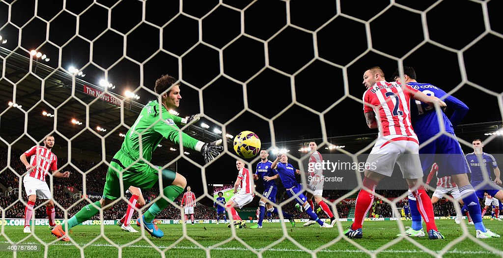 Chelsea player John Terry (c) heads in the opening goal past Stoke goalkeeper Asmir Begovic during the Barclays Premier League match between Stoke City and Chelsea at Britannia Stadium on December 22, 2014 in Stoke on Trent, England.