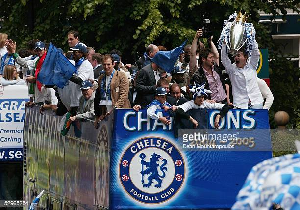 Chelsea players display the FA Barclays Premier League trophy and League Cup on team bus as they are surrounded by fans as they make their way down...