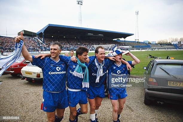 Chelsea players from left Graham Roberts Kevin Wilson Peter Nicholas and an unidentified player celebrate whilst avoiding the pitch side parked cars...