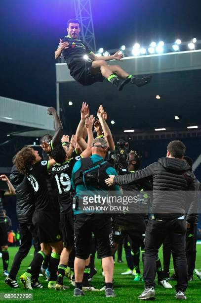 Chelsea players throw their Spanish midfielder Pedro in the air as they celebrate being confirmed Premier League champions after the English Premier...
