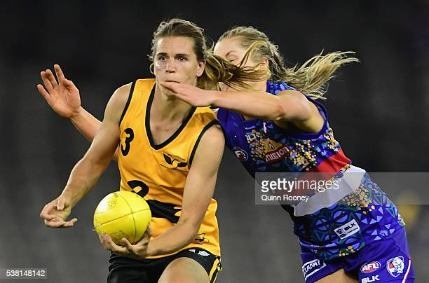 Chelsea Randall of Western Australia handballs whilst being tackled by Kaitlyn Ashmore of the Bulldogs during the Western Bulldogs v West Australia...
