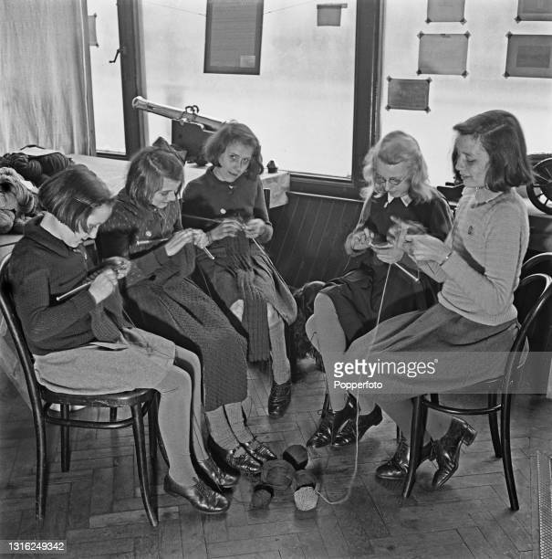 Chelsea schoolgirls Avis and Enid Turner, Sheila and Mary Hennick and Adrianna Seward knit scarves and jumpers to keep British Army troops warm at a...