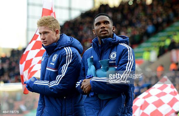 Chelsea substitutes Kevin De Bruyne and Samuel Eto'o walk out onto the pitch clutching hotwater bottles during the Barclays Premier League match...