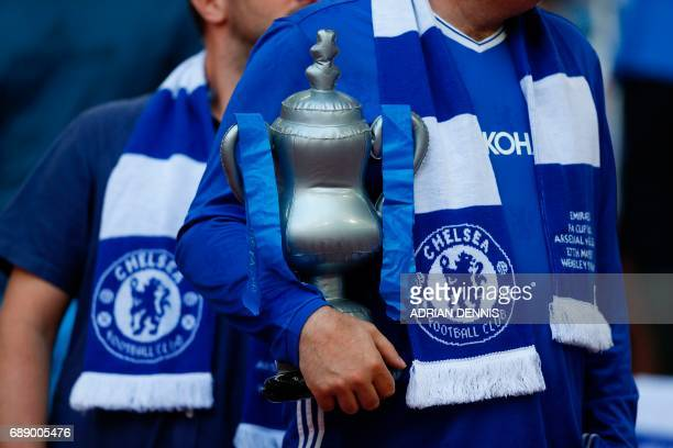 A Chelsea supporter holds an inflatable FA Cup trophy in the crowd ahead of the English FA Cup final football match between Arsenal and Chelsea at...
