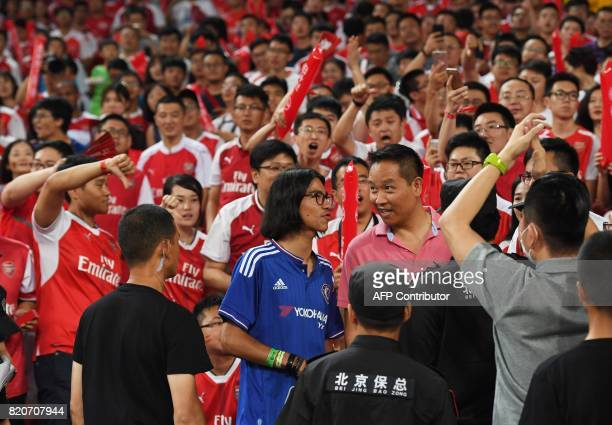 A Chelsea supporter talks with an official after attempting to sit amongst Arsenal fans before the start of their preseason football match against...