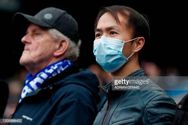A Chelsea supporter wearing PPE including a face mask as a precautionary measure against COVID19 awaits kick off in the English Premier League...