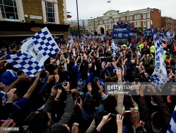 Chelsea supporters take pictures of the team as they leave Stamford Bridge on an open top bus during the Chelsea victory parade following their UEFA...