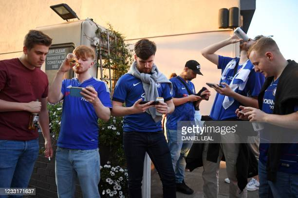 Chelsea supporters watch the game on their mobile phones in the street during the UEFA Champions League final football match between Manchester City...