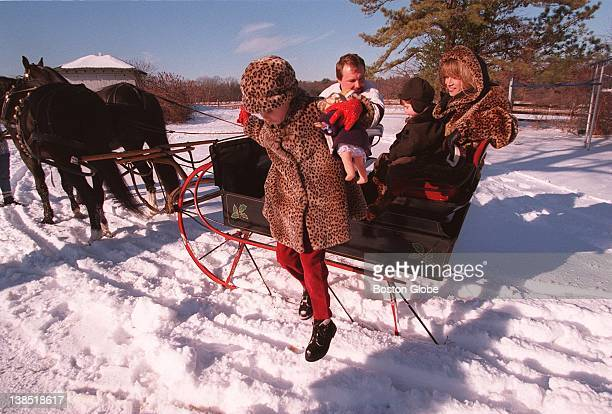 Chelsea Tallarico leaps down from the carriage after her younger brother Taj and mother Teresa took a ride with Shawn Hennigan in the woods of North...