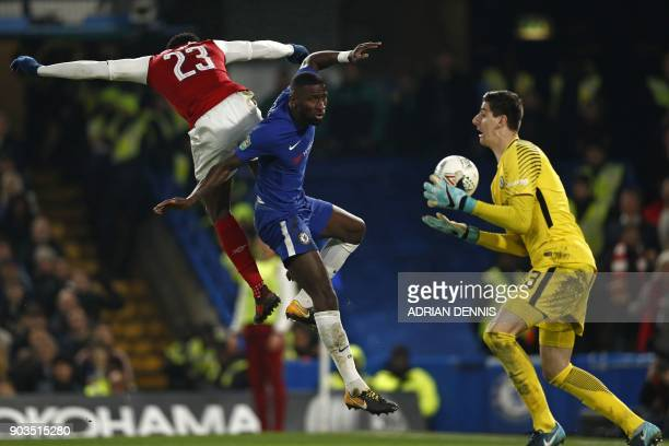 Chelsea's Belgian goalkeeper Thibaut Courtois catches the ball as Arsenal's English striker Danny Welbeck vies with Chelsea's German defender Antonio...