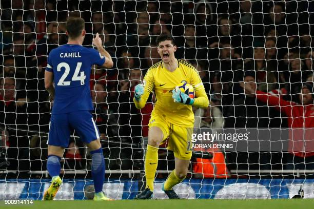 Chelsea's Belgian goalkeeper Thibaut Courtois celebrates saving a shot with Chelsea's English defender Gary Cahill during the English Premier League...