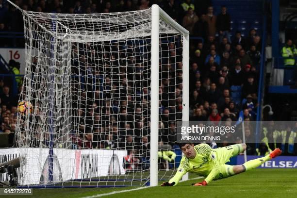 Chelsea's Belgian goalkeeper Thibaut Courtois dives but fails to stop the header from Swansea City's Spanish striker Fernando Llorente for Swansea's...