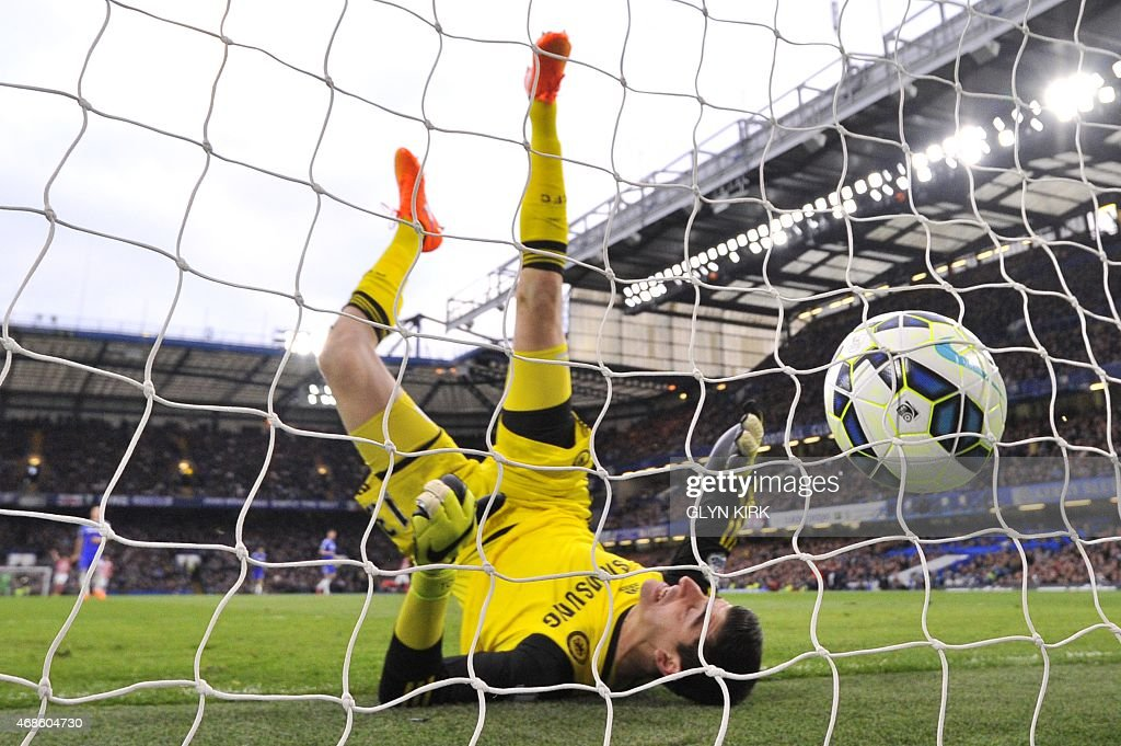 Chelsea's Belgian goalkeeper Thibaut Courtois falls after failing to keep out a long range goal from Stoke City's Scottish midfielder Charlie Adam (unseen) to equalise 1-1 during the English Premier League football match between Chelsea and Stoke City at Stamford Bridge in London on April 4, 2015. USE. No use with unauthorized audio, video, data, fixture lists, club/league logos or live services. Online in-match use limited to 45 images, no video emulation. No use in betting, games or single club/league/player publications.