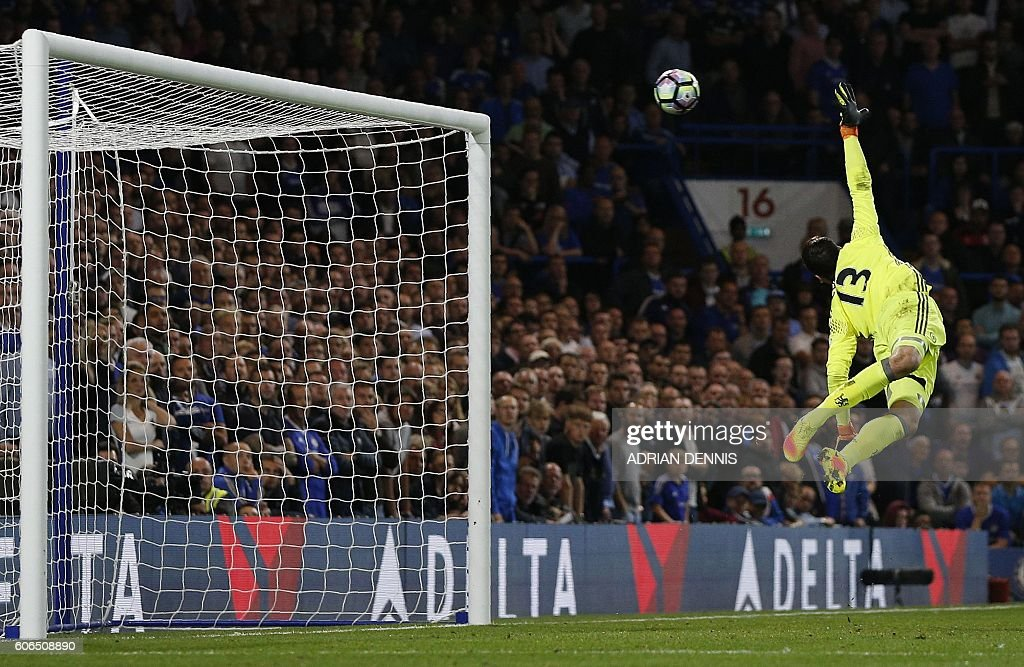 TOPSHOT - Chelsea's Belgian goalkeeper Thibaut Courtois jumps but fails to to save a long-range shot from Liverpool's English midfielder Jordan Henderson to score his team's second goal during the English Premier League football match between Chelsea and Liverpool at Stamford Bridge in London on September 16, 2016. / AFP / Adrian DENNIS / RESTRICTED TO EDITORIAL USE. No use with unauthorized audio, video, data, fixture lists, club/league logos or 'live' services. Online in-match use limited to 75 images, no video emulation. No use in betting, games or single club/league/player publications. /