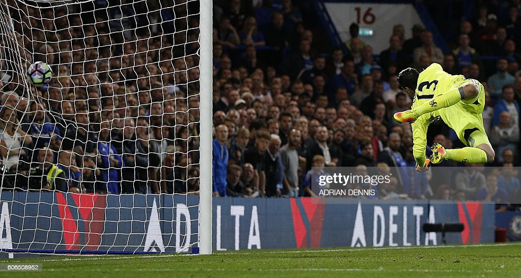 Chelsea's Belgian goalkeeper Thibaut Courtois jumps but fails to to save a long-range shot from Liverpool's English midfielder Jordan Henderson to score his team's second goal during the English Premier League football match between Chelsea and Liverpool at Stamford Bridge in London on September 16, 2016. / AFP / Adrian DENNIS / RESTRICTED TO EDITORIAL USE. No use with unauthorized audio, video, data, fixture lists, club/league logos or 'live' services. Online in-match use limited to 75 images, no video emulation. No use in betting, games or single club/league/player publications. /