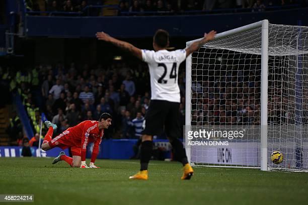 Chelsea's Belgian goalkeeper Thibaut Courtois looks back at the ball in the back of his net as Queens Park Rangers' Chilean striker Eduardo Vargas...