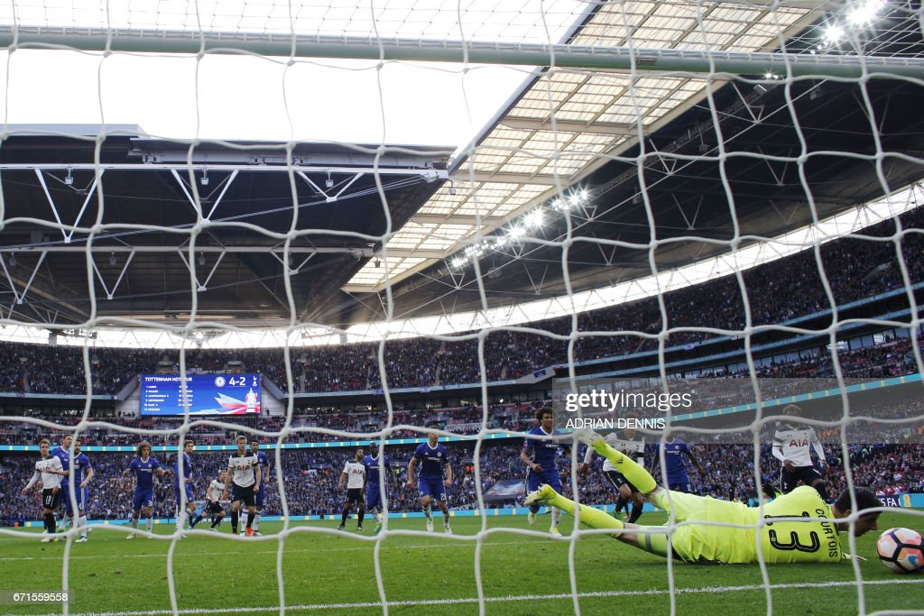 Chelsea's Belgian goalkeeper Thibaut Courtois (R) saves a goal off Tottenham Hotspur's English striker Harry Kane's free kick during the FA Cup semi-final football match between Tottenham Hotspur and Chelsea at Wembley stadium in London on April 22, 2017. / AFP PHOTO / Adrian DENNIS / NOT