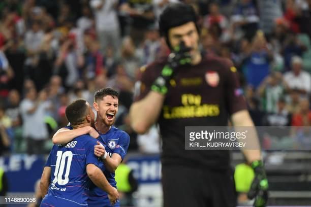 Chelsea's Belgian midfielder Eden Hazard celebrates with Chelsea's Italian midfielder Jorginho as Arsenal's Czech goalkeeper Petr Cech reacts after...