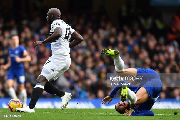 Chelsea's Belgian midfielder Eden Hazard falls to the floor after a challenge by Fulham's French striker Aboubakar Kamara during the English Premier...