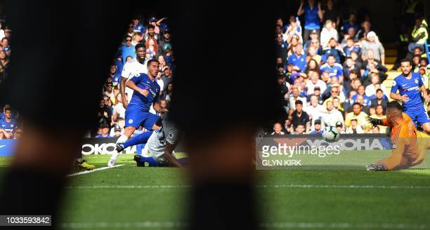 Chelsea's Belgian midfielder Eden Hazard is pictured throught the legs of the linesman as he scores his team's second goal during the English Premier...