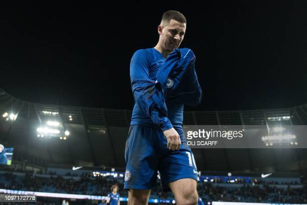 Chelsea's Belgian midfielder Eden Hazard removes his shirt before giving it to a fan after the English Premier League football match between...