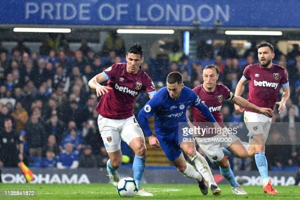 Chelsea's Belgian midfielder Eden Hazard runs past West Ham United's Paraguayan defender Fabián Balbuena and West Ham United's English midfielder...