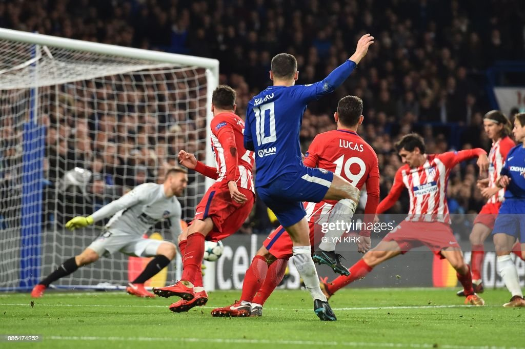 TOPSHOT - Chelsea's Belgian midfielder Eden Hazard (L) shoots goalward and Atletico Madrid's Montenegrin defender Stefan Savic (R) blocks to score an own goal during a UEFA Champions League Group C football match between Chelsea and Atletico Madrid at Stamford Bridge in London on December 5, 2017. / AFP PHOTO / Glyn KIRK