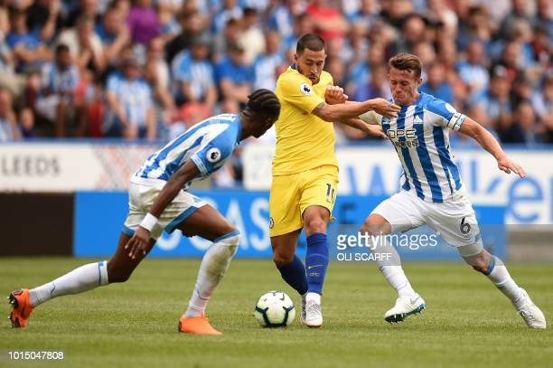 Chelsea's Belgian midfielder Eden Hazard vies with Huddersfield Town's Swissborn Dutch defender Terence Kongolo and Huddersfield Town's English...