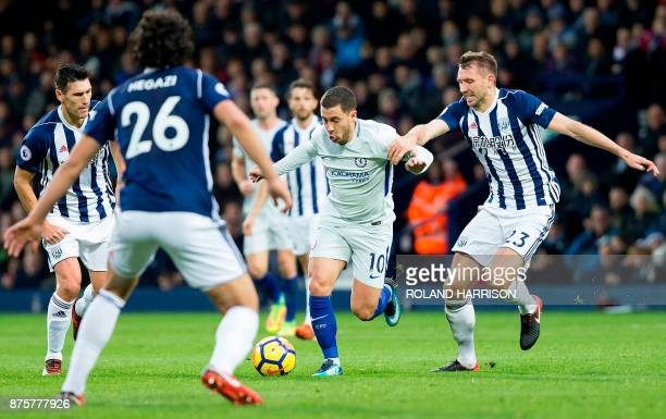 Chelsea's Belgian midfielder Eden Hazard vies with West Bromwich Albion's Northern Irish defender Gareth McAuley and West Bromwich Albion's Egyptian...