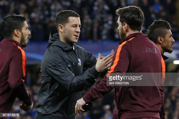 Chelsea's Belgian midfielder Eden Hazard winks at Barcelona's Argentinian striker Lionel Messi as they shake hands ahead of the first leg of the UEFA...
