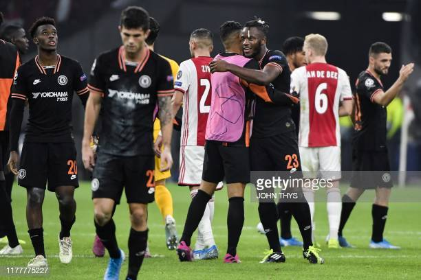 Chelsea's Belgian striker Michy Batshuayi is congratulated by teamplayers at the end of the UEFA Champions League Group H football match between Ajax...