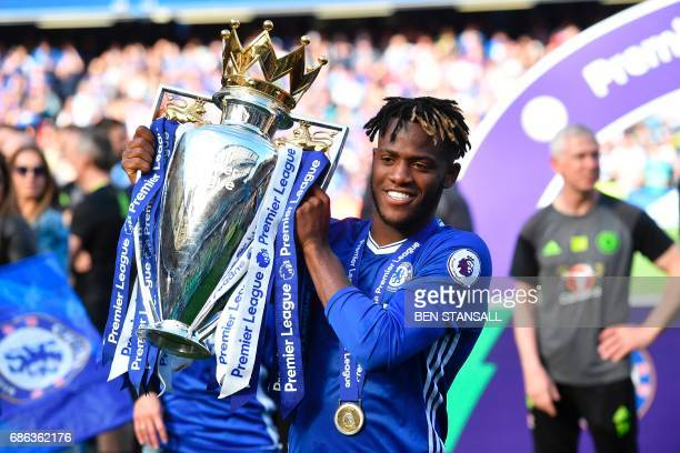 Chelsea's Belgian striker Michy Batshuayi poses with the English Premier League trophy as players celebrate their league title win at the end of the...