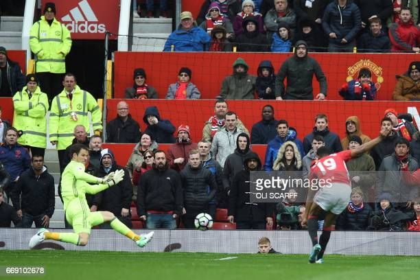 Chelsea's Bosnian goalkeeper Asmir Begovic tries to defend as Manchester United's English striker Marcus Rashford scores the opening goal during the...