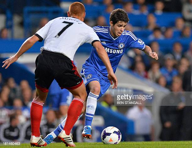 Chelsea's Brazilian midfielder Oscar vies for the ball with Fulham's English midfielder Steve Sidwell during the English Premier League football...