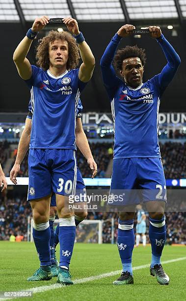 Chelsea's Brazilian midfielder Willian and Chelsea's Brazilian defender David Luiz hold up their black armbands as they celebrate Willian scoring his...