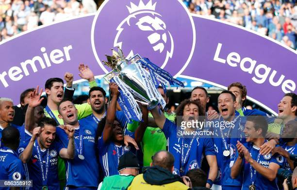 Chelsea's Brazilian midfielder Willian and Chelsea's Brazilian defender David Luiz hold up the Premier League trophy as players celebrate their...