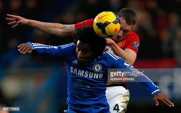 Chelsea's Brazilian midfielder Willian and Manchester United's English defender Phil Jones contest a high ball during the English Premier League...