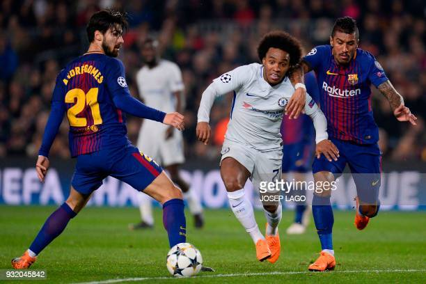 Chelsea's Brazilian midfielder Willian challenges Barcelona's Brazilian midfielder Paulinho and Barcelona's Portuguese midfielder Andre Gomes during...