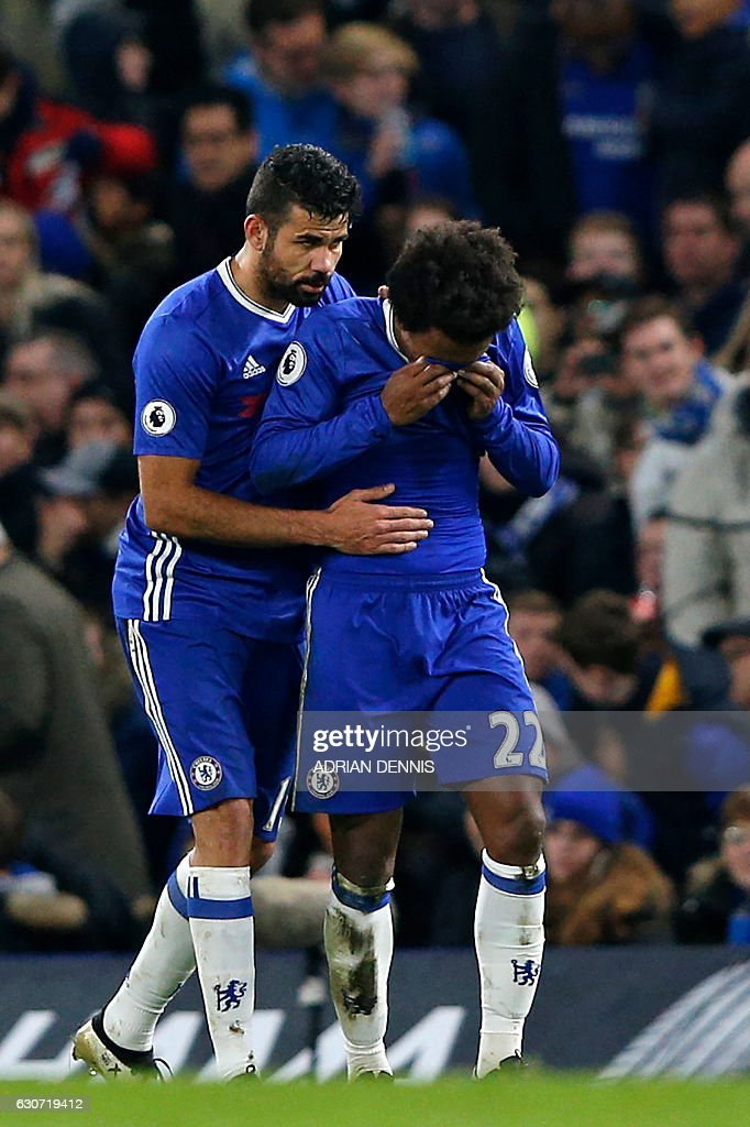 Chelsea's Brazilian midfielder Willian (R) is consoled by Chelsea's Brazilian-born Spanish striker Diego Costa as he reacts after scoring a goal during the English Premier League football match between Chelsea and Stoke City at Stamford Bridge in London on December 31, 2016. / AFP / Adrian DENNIS / RESTRICTED TO EDITORIAL USE. No use with unauthorized audio, video, data, fixture lists, club/league logos or 'live' services. Online in-match use limited to 75 images, no video emulation. No use in betting, games or single club/league/player publications. /
