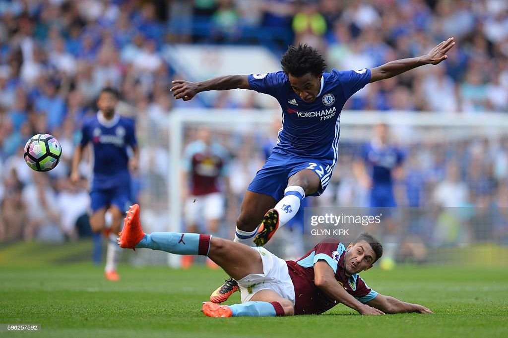 TOPSHOT - Chelsea's Brazilian midfielder Willian jumps a tackle during the English Premier League football match between Chelsea and Burnley at Stamford Bridge in London on August 27, 2016. / AFP / GLYN KIRK / RESTRICTED TO EDITORIAL USE. No use with unauthorized audio, video, data, fixture lists, club/league logos or 'live' services. Online in-match use limited to 75 images, no video emulation. No use in betting, games or single club/league/player publications. /