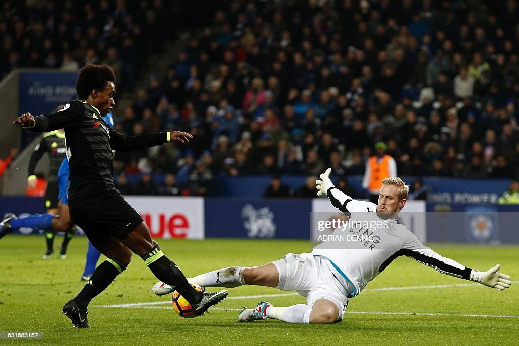 Chelsea's Brazilian midfielder Willian (L) passes the ball as Leicester City's Danish goalkeeper Kasper Schmeichel comes out to block in the build up to their third goal during the English Premier League football match between Leicester City and Chelsea at King Power Stadium in Leicester, central England on January 14, 2017. Cheslea won the game 3-0. / AFP / Adrian DENNIS / RESTRICTED TO EDITORIAL USE. No use with unauthorized audio, video, data, fixture lists, club/league logos or 'live' services. Online in-match use limited to 75 images, no video emulation. No use in betting, games or single club/league/player publications. /