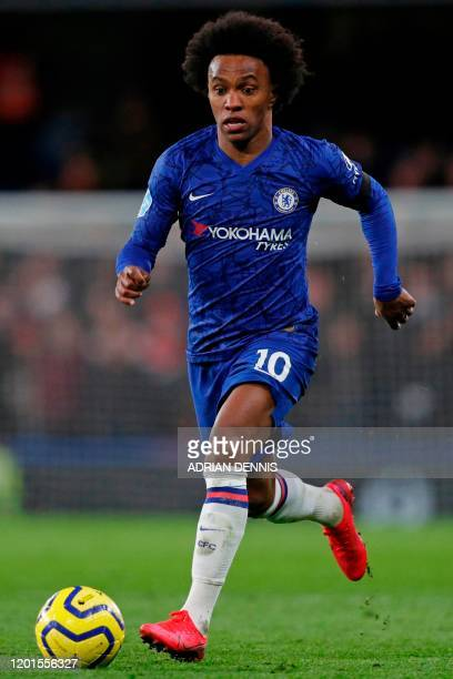 Chelsea's Brazilian midfielder Willian runs with the ball during the English Premier League football match between Chelsea and Manchester United at...
