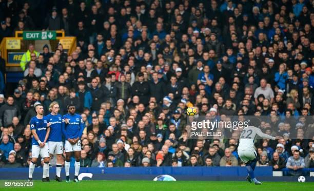 Chelsea's Brazilian midfielder Willian takes a free kick over the defensive wall of Everton's French midfielder Morgan Schneiderlin Everton's English...