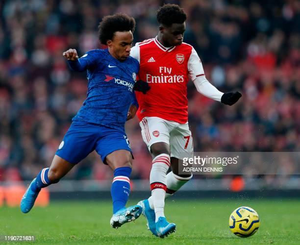 Chelsea's Brazilian midfielder Willian tangles with Arsenal's English striker Bukayo Saka during the English Premier League football match between...