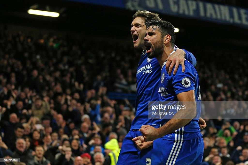 Chelsea's Brazilian-born Spanish striker Diego Costa celebrates with Chelsea's Spanish defender Marcos Alonso (L) after scoring their fourth goal during the English Premier League football match between Chelsea and Stoke City at Stamford Bridge in London on December 31, 2016. Chelsea won the game 4-2. / AFP / Ian KINGTON / RESTRICTED TO EDITORIAL USE. No use with unauthorized audio, video, data, fixture lists, club/league logos or 'live' services. Online in-match use limited to 75 images, no video emulation. No use in betting, games or single club/league/player publications. /